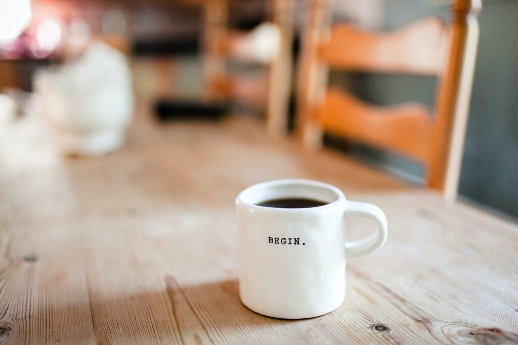 Photo of coffee mug saying 'begin' by Danielle MacInnes on Unsplash